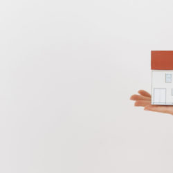 close-up-of-human-hand-holding-mini-house-model-on-white-backdrop